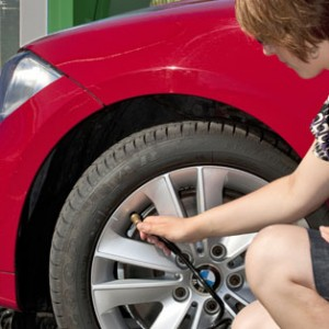 Woman Checking Tyre Pressure